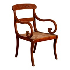Antique Javanese Wooden Armchair with Carved Back, Curving Arms and Rattan Seat