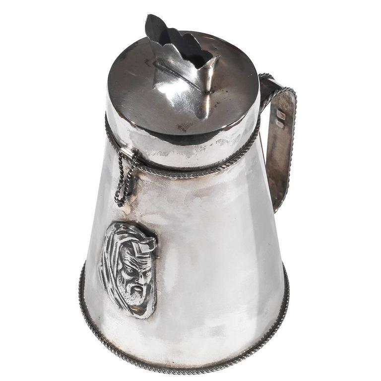 Russia, silversmith monogram Cyrillic M. F. dated 1896   Silver tankard-form charity box. The front applied with embossed plaque depicting a rabbi, the cover with latch and insert for the coins, scroll handles,  Marked on base and handles with