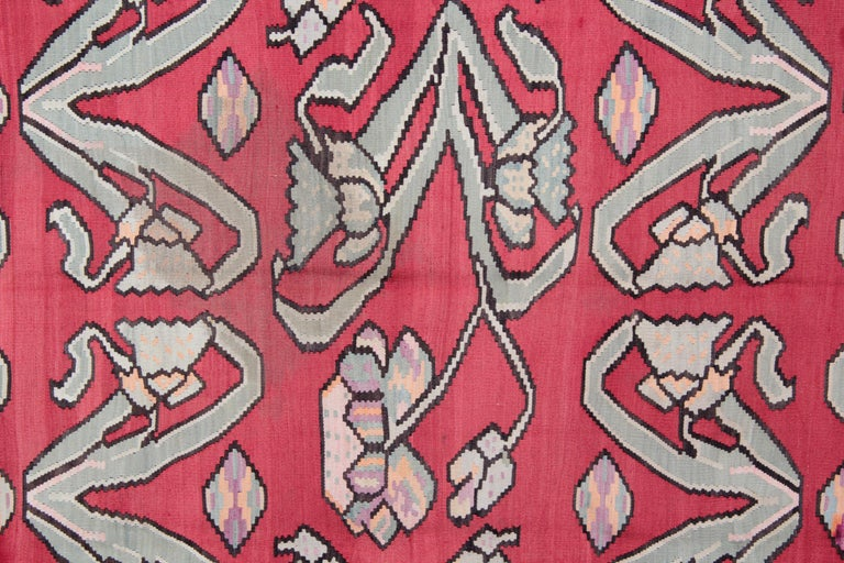This colorful Turkish carpet rug is woven by very skilled weavers in Turkey, who used the highest quality wool and cotton. The flat-weave rug has light blue, orange Salmon, green, white, pink, black and brown colors. The pink rug background of this