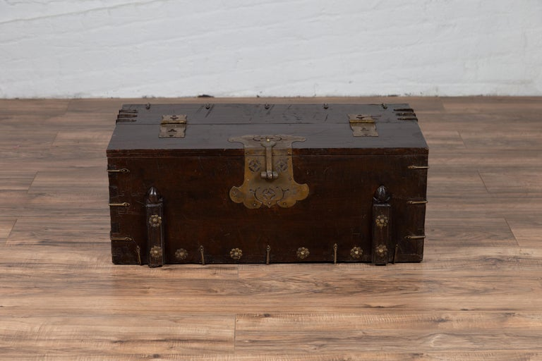An antique Korean wooden chest from the early 20th century, with cut brass hardware and folding top. Born in Korea during the early years of the 20th century, this small wooden chest features a linear silhouette, perfectly accented with cut brass
