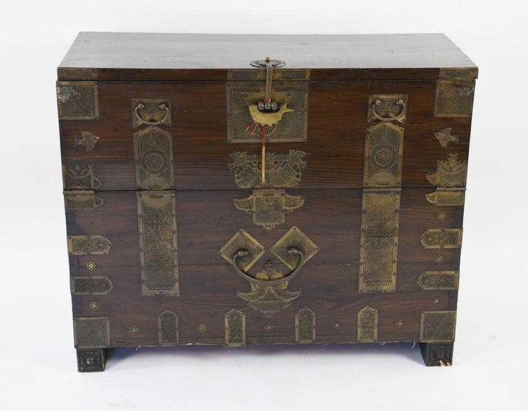 The antique Korean Bandaji, or blanket chest is handcrafted in wood and embellished with original brass trim, mounted with intricate fittings, including handles, hinges and lock plate. Chest has a drop front, used to store clothing and documents on