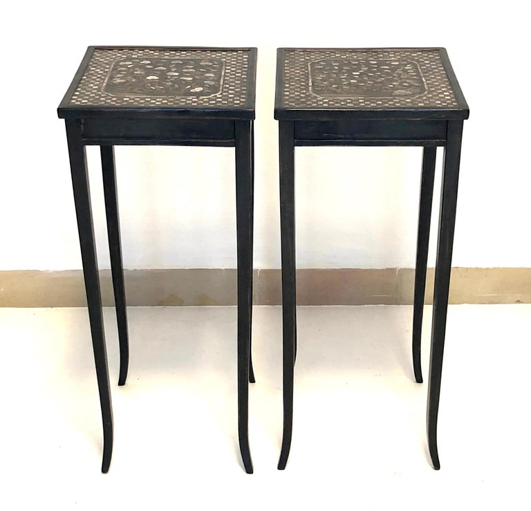 Extremely rare small pair of 19th century black lacquer tables with rare 17th century table tops. The table tops are decorated with mother of pearl inlay and date from the Momoyama period of 17th century Japan. The chequer board outer edge surrounds