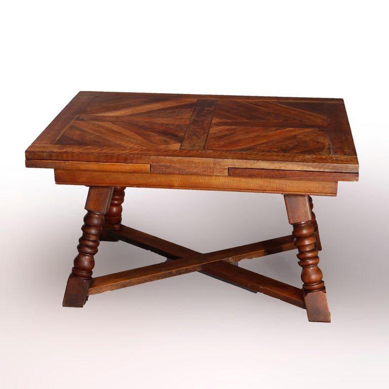An antique and large continental draw-top dining table offers walnut construction with parquetry inlaid top with two leaves, raised on splayed turned legs having X-stretcher base, 19th century  Measures: 29.25