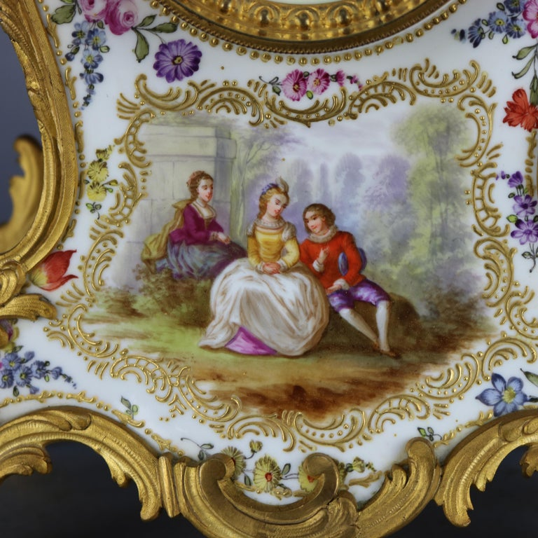 An antique and large French Louis XVI (elements of Rococo) mantel clock offers hand painted porcelain case with overall detached floral spray and reserve depicts courting couple in countryside setting, gilt cast bronze scroll and foliate mounts