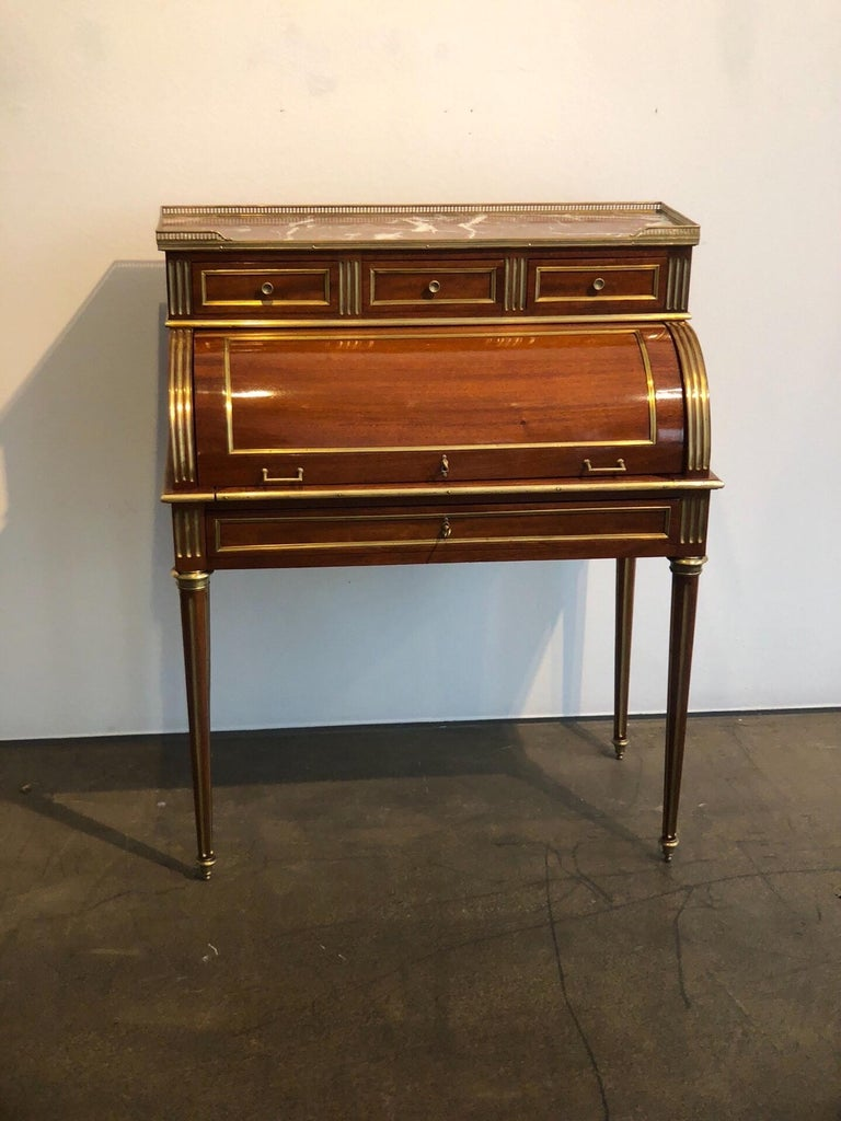 Very elegant antique French Louis XVI style cylinder writing desk from the 19th century. The excellent craftsmanship and high-grade materials, such as polished brass, polished mahogany, leather, and marble, underlines the beauty of this