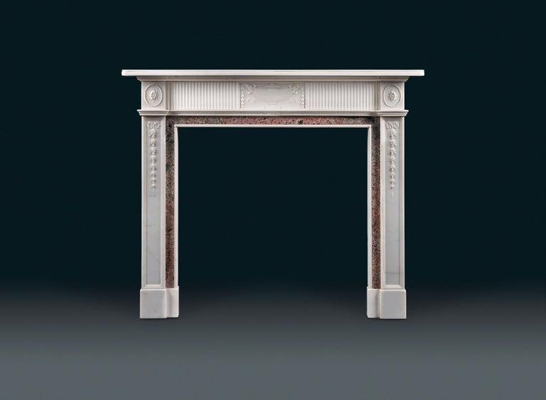 An antique late 19th century statuary and tiree marble fireplace, the fluted frieze centred with a tablet carved with a lidded urn with flower drop husks falling from the handles. The end blockings with circular flower heads, the panelled pilaster