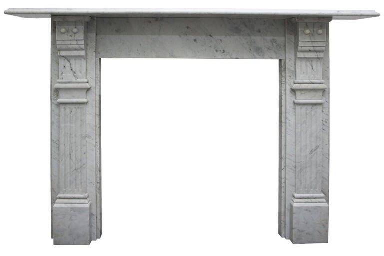 Antique Victorian Carrara marble fireplace surround with fluted jambs terminating in fluted and stepped corbels supporting the shelf, circa 1880. Pictured with an original Victorian cast iron arched insert, sold separately.