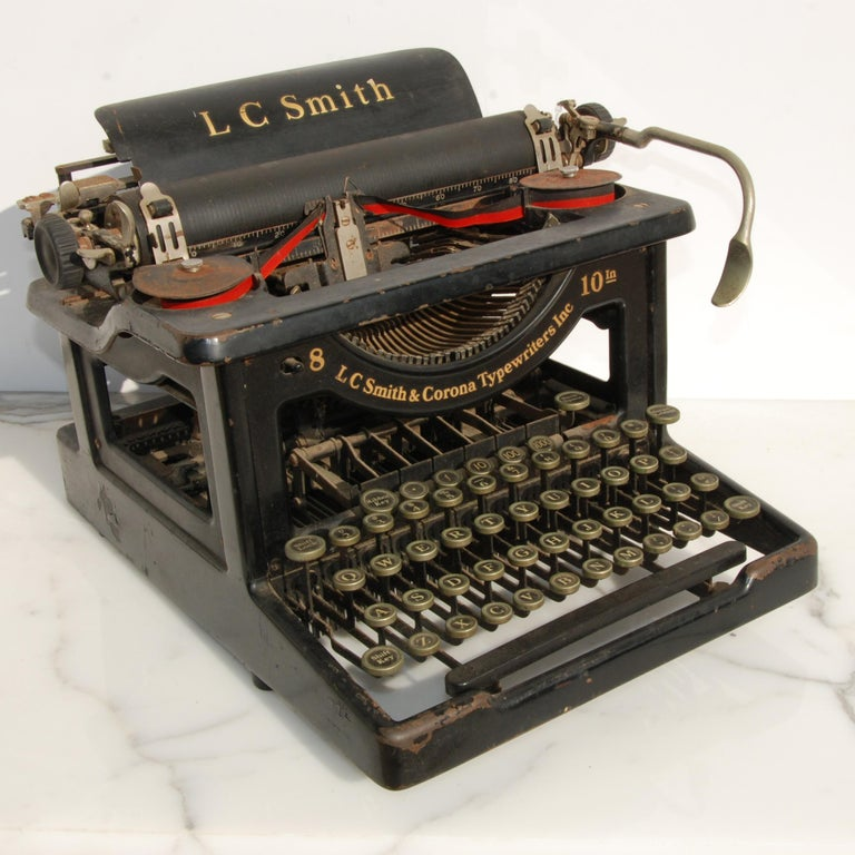 This is an original LC Smith & Corona Typewriter #8 10 with a 10 inch carriage and an open-frame design. The keys are nickel with white face and black numbers. Four rows of keys with a top row of decimals. Keys stick slightly, but can still be typed
