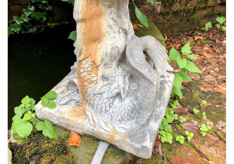 Antique garden figure of Triton with his scrolled dolphin tail blows into a shell shaped horn that forms the fountain. On a square base. Measures: height 28