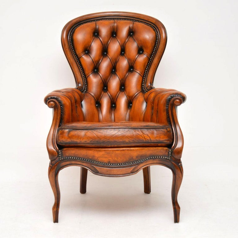 This antique French spoon back armchair still has the original deep buttoned leather upholstery on it. Our leather specialist has revived, polished and enhanced the color, so it still has a lot of character. It's in excellent condition, dating from