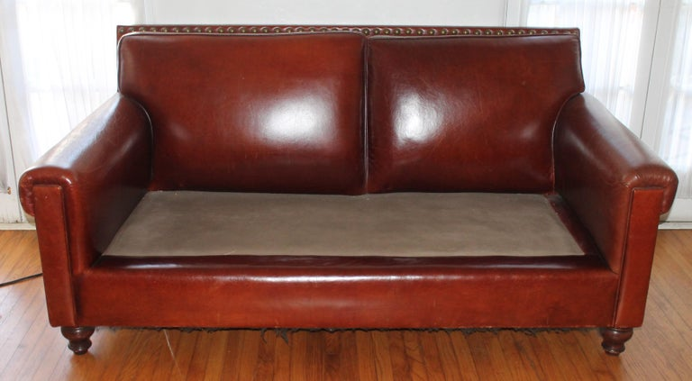 Vintage leather sofa with custom-made fabric cushion. This sofa has the reconditioned leather and original nail head tacks. The sofa is super comfortable.