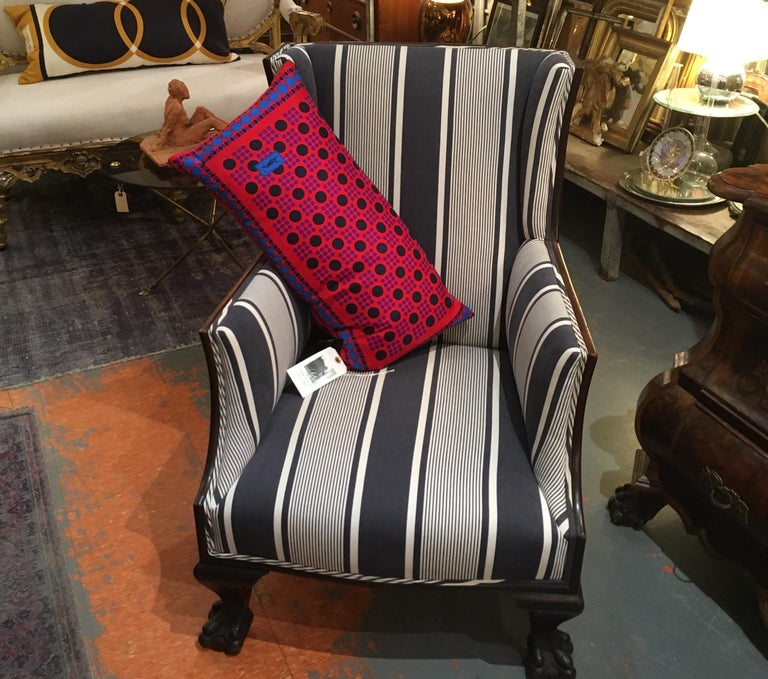 Antique English chair with stately hand carved wood lion paw feet. Newly professionally reupholstered in crisp antique blue and white stripe fabric from France.