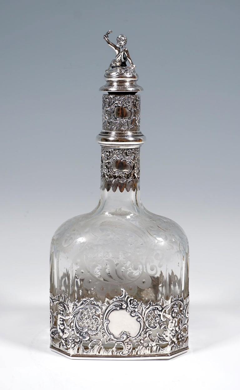 Elaborately crafted liqueur bottle made of clear glass on a rectangular floor plan with bevelled corners, in the stand area and on the slender neck framed by openwork silver fittings with cartouches, rocailles and putti,  cork closure piece with
