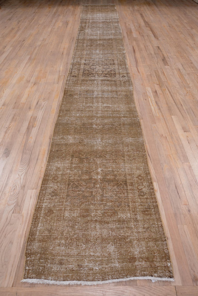 This rather severely all-over worn west Persian village runner shows a bi tonal palette of light and medium warm brown in a typical Herati pattern. The field abrashes to a darker brown near the centre.