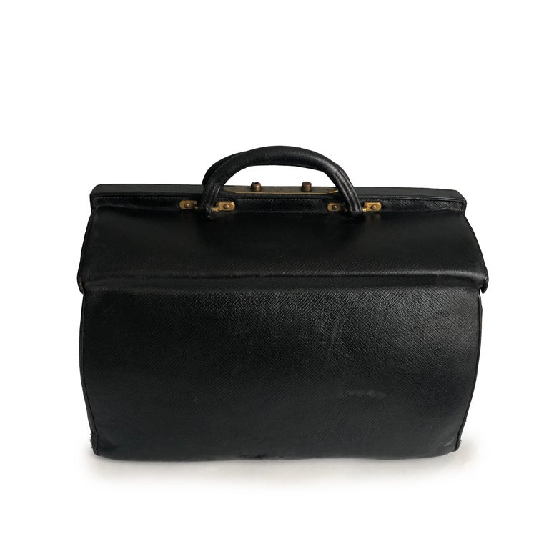 Antique Louis Vuitton Sac Cabine Black Doctors Bag, likely made in the early 20th C.  Made from black textured grain leather, it opens like a doctor's bag with two hinged pieces and features double top handles.  Lined in red leather with two flat