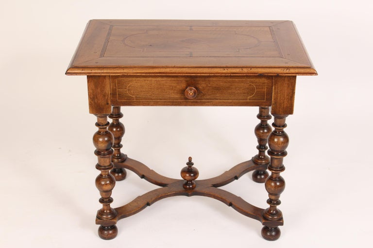 Antique Louis XIV style walnut occasional table, 19th century. With an inlaid top, X-shaped stretcher bar, turned legs and dovetail construction on the drawer.
