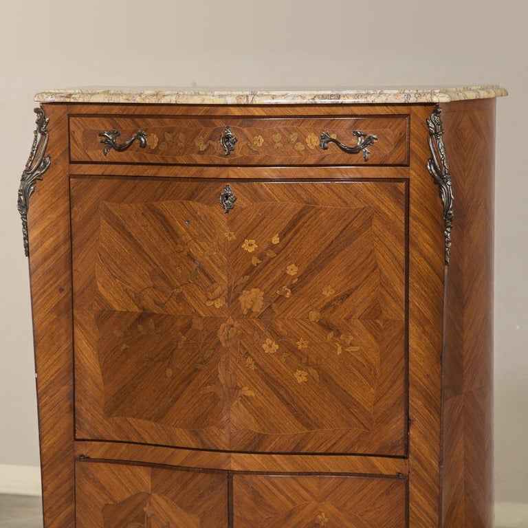 Crafted from exotic imported mahogany with precisely oriented grain patterns, this secretary features floral and foliate marquetry on the upper drawer; drop front desk surface and lower cabinet doors. Contoured cornerposts have been adorned with