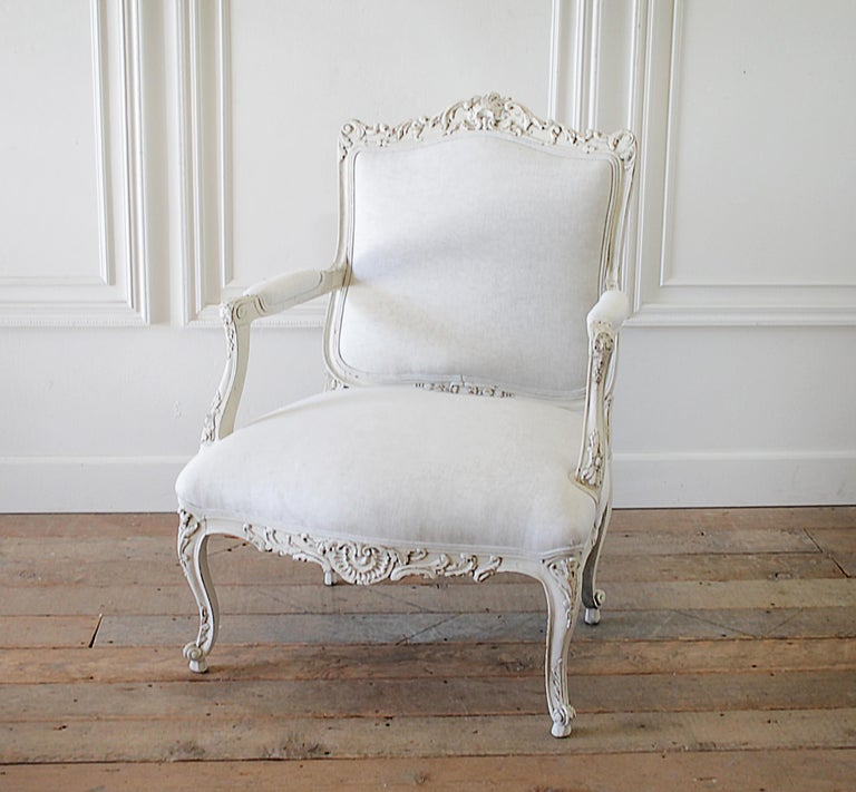 Antique Louis XV style French painted and upholstered open arm chair Painted in a soft white, with subtle distressed antique patina. We reupholstered this in natural Belgian linen that has a more greige tone. Beautiful Rococo style carvings, a