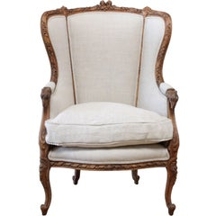 Antique Louis XV Style Carved Wing Chair Upholstered in Natural Linen