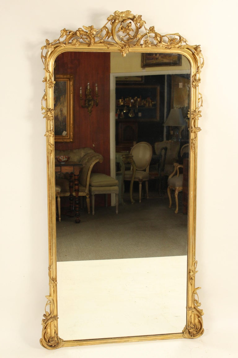Antique Louis XV style giltwood and composition mirror with floral and c scroll designs, 19th century. This mirror has old gold leaf with some paint touch up. This mirror is very heavy and will require and professional to hang it.