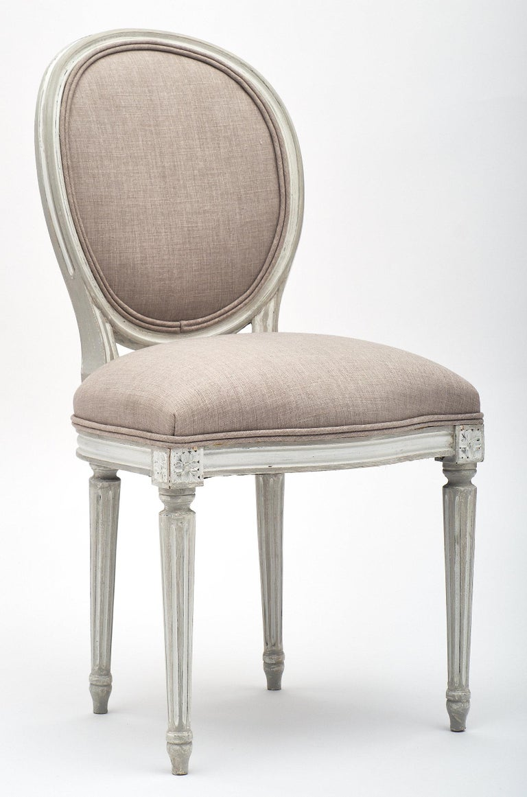 Elegant Louis XVI style antique dining chairs with medallion backs. The set of six has been newly upholstered in a dove grey linen fabric. The frames are made of beech wood that has been hand-painted with a milk paint. The tapered legs are fluted,