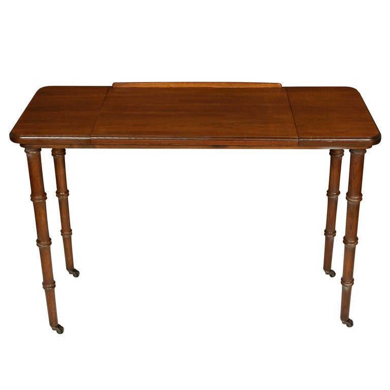 Antique mahogany architect's table with bamboo shaped legs and caster wheels.