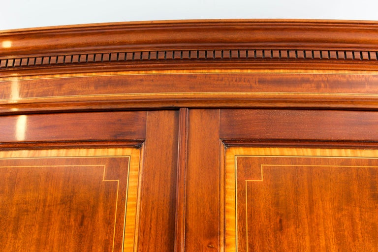 This is an impressive antique English Victorian Sheraton style mahogany wardrobe by the world-famous British furniture maker, Maple & Co., circa 1890 in date.  This beautiful bow-fronted two-door wardrobe features an exquisite dentil cornice above
