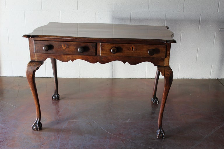 Beautifully proportioned cabriole leg 18th century English mahogany table with two drawers, two false drawers, and carved claw feet.