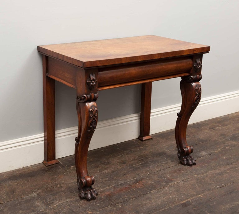 An antique mahogany console table of fine quality and proportions. The two front scrolled legs with carved knees terminate with paw feet. The pull-out drawer with a barrel shaped front is flanked by carved floral end-blocks.