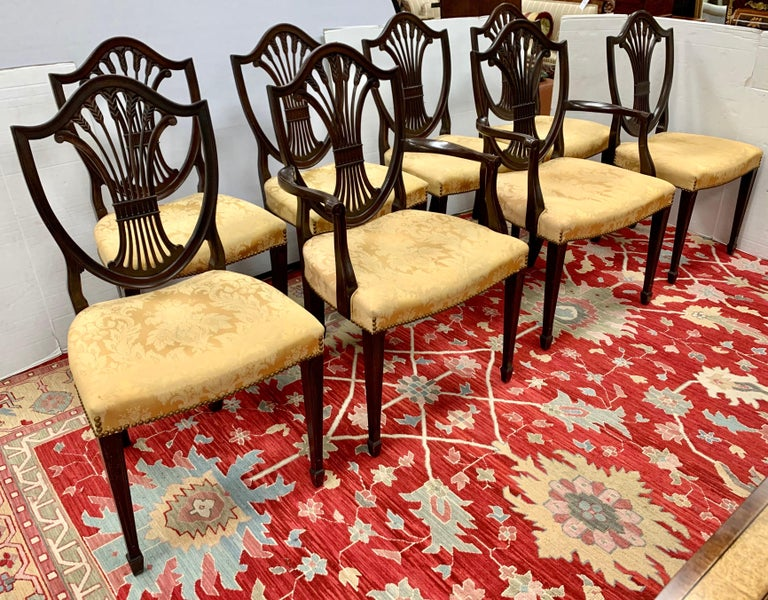 Fine set of antique carved mahogany Hepplewhite dining chairs circa, 1900 consisting of two arm chairs and six side chairs all with striking shield shaped backs and decorative pierced back splats with a wheat sheaf design. They are upholstered in a