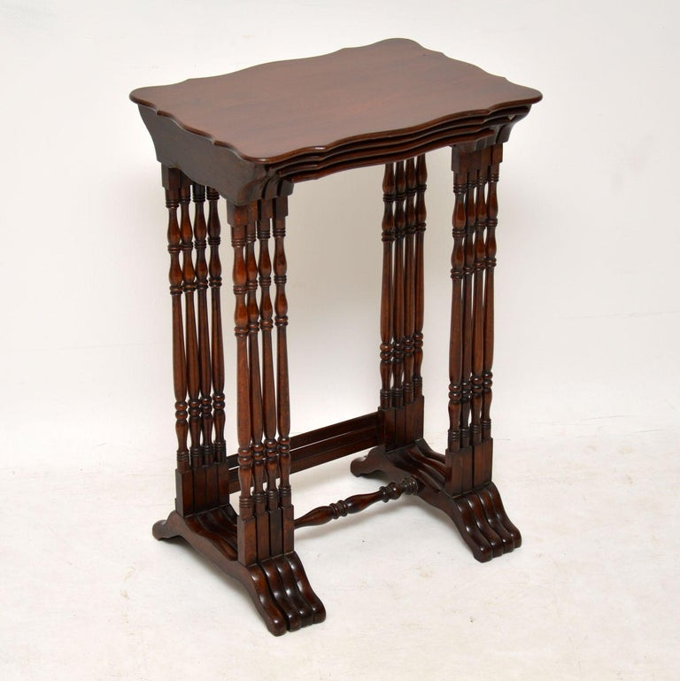 Antique solid mahogany nest of four tables in excellent condition, dating from the 19th century. The tops are shaped all the way around & the tall legs are beautifully turned. There are cross stretchers at the base which help keep them more stable &