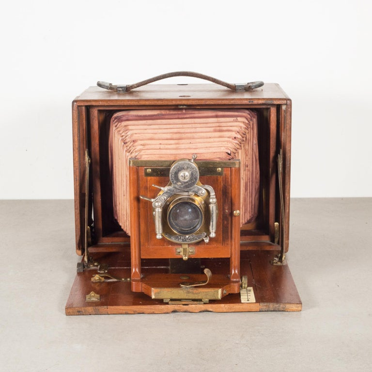About  An original Premo long focus folding camera with a brass and leather strap, Mahogany case and Mahogany front. Camera folds open and closes properly.  Camera is sold for decorative purposes only.  CreatorRochester Optical Co. Date of