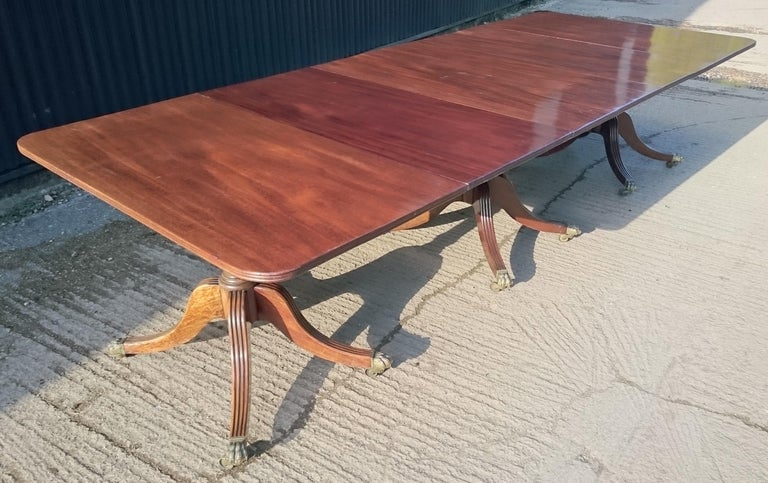 George III period antique dining table standing on three four splay legs. The edge of the top and the top of the legs are reeded all round and the legs terminate in an especially elegant the caster cup. The top of this table is good and flat and the