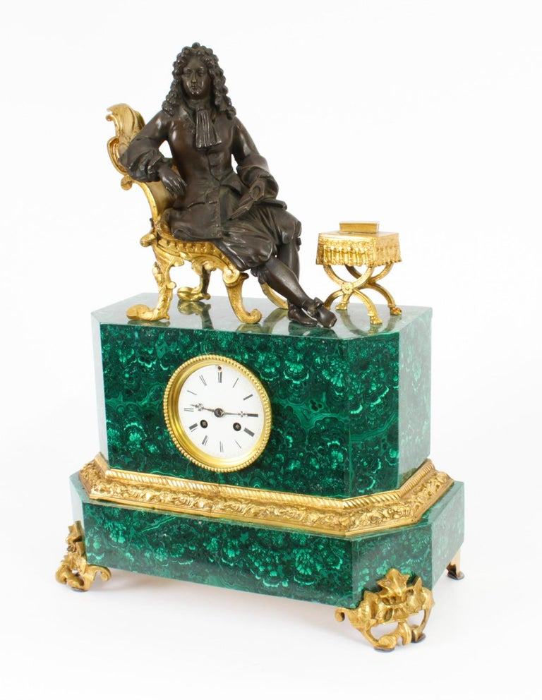 This is a superb quality antique French malachite, bronze and ormolu mantel clock dating from Circa 1850 in date.  It features Louis XVI seated on an ormolu throne chair whilst reading a book.  The clockmakers name is inscribed on the backplate.
