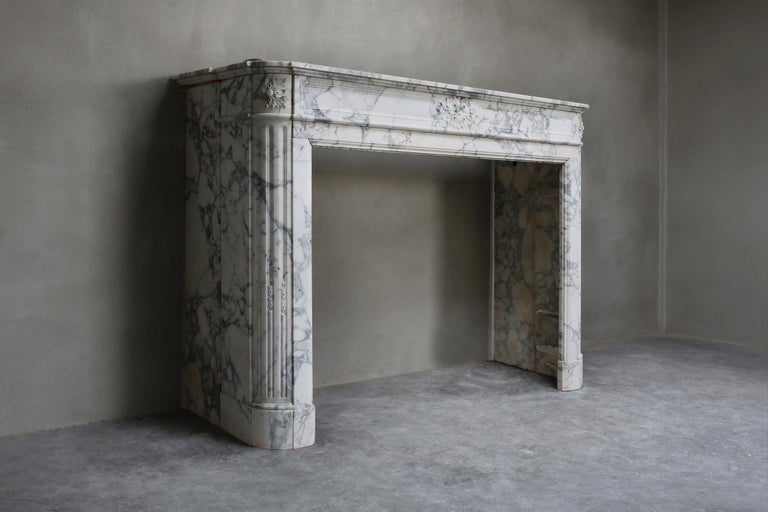 Beautiful antique fireplace made of Arabescato marble from Italy. This old French fireplace is in Louis XVI style and dates from the 19th century! Arabescato is a beautiful white marble with light veins. The mantelpiece has beautiful round shapes