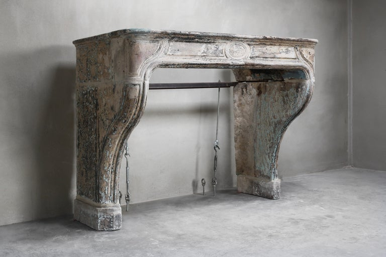 Antique French fireplace from the 19th century in the style of Louis XIV. The fireplaces in style of Louis XIV are often characterized by the curves and lines. With this patinated fireplace you can see the history very well. The color scheme is also