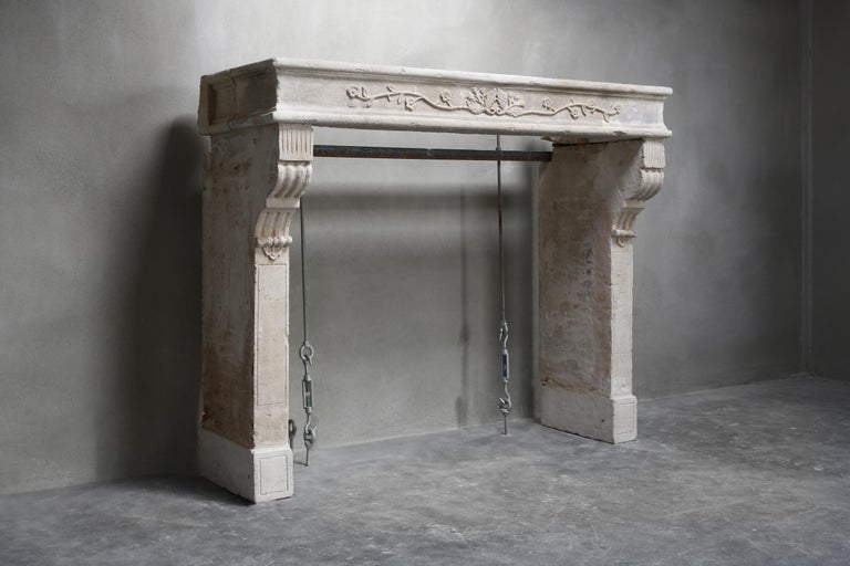 Beautiful decorative antique fireplace of French limestone from the 19th century. The antique fireplace is in the style of Louis XVI and has an ornament with leaves in the middle of the upper part. You can see the cannelures on the legs. An antique