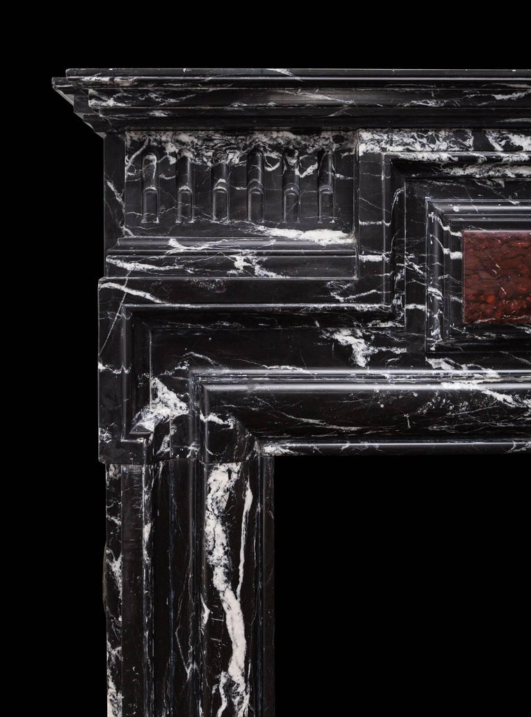 Antique Belgian marble fireplace in the Baroque Revival style. Made in a black and white Nero Marquina marble with a Rouge Griotte centre panel. A bolection moulding frames the opening, with fluted frieze panels and a deep mantel shelf on top.