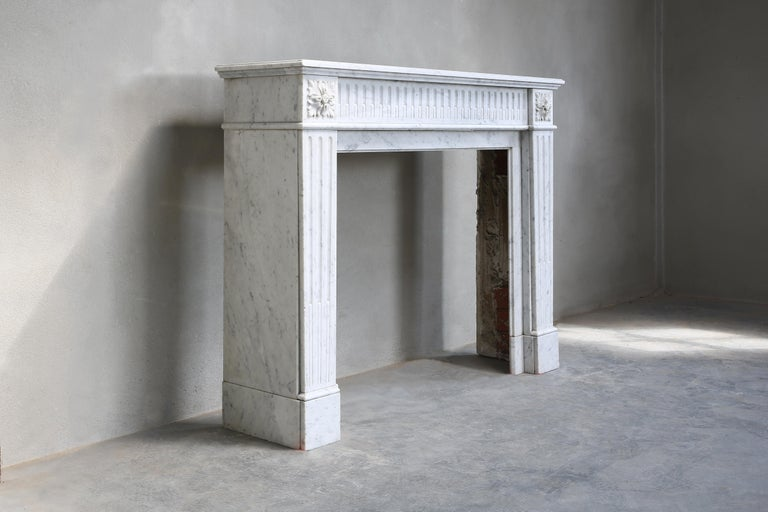 Beautiful antique fireplace of Carrara marble from the 19th century. This fireplace is from Paris and is in the style of Louis XVI. The fireplace is richly decorated with flutes in the front part and on the legs. A chic model that will fit perfect