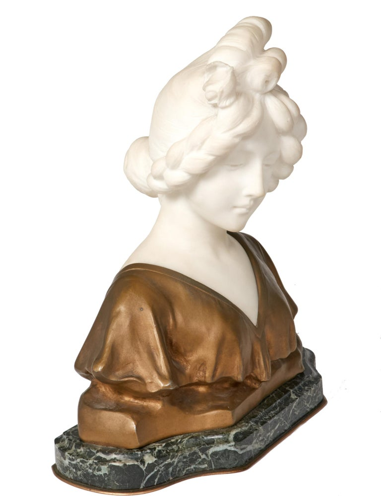 Graceful marble and bronze bust of a demure young woman by listed French/Italian artist Affortunato Gory (1895-1925). Beautifully rendered bust in marble with her hair pulled back and wearing a draped gown sculpted from bronze. Presented on a dark