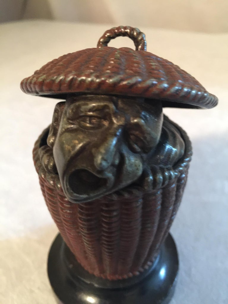 This most unusual match safe features this poor fellow peeking out of a basket that will hold your matches. I should think the match safe is the least important characteristic of this item. His face is quite fascinating and whimsical. I don't