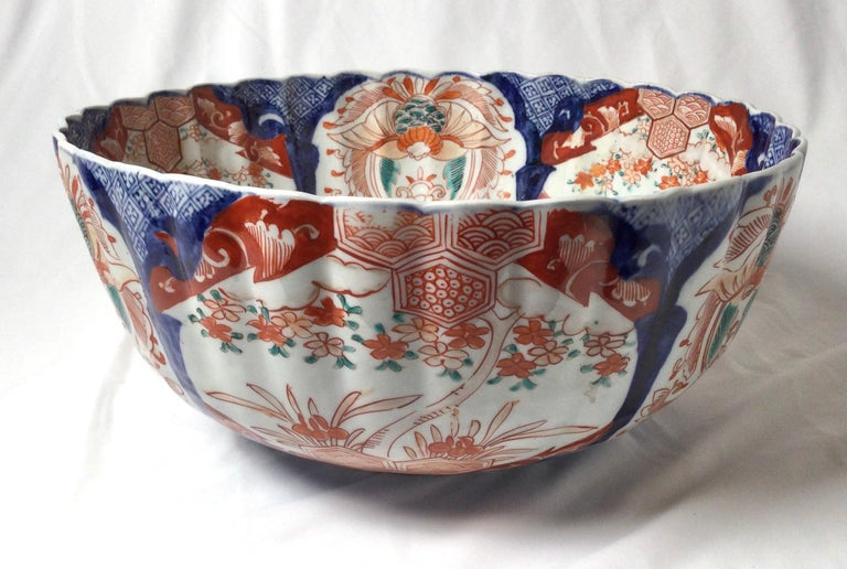 Classic cobalt blue and iron red Imari scalloped bowl with scalloped rim. The white porcelain with Japanese hand painted decoration with green accents. Measure: Large 13.5 inches in diameter.