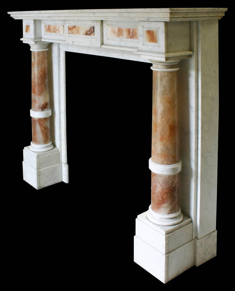 Mid-19th century continental Carrara marble fire surround, the substantial alabaster pillars support the box frieze which is decorated with alabaster mounts and is in turn surmounted by the heavily moulded shelf, circa 1870.