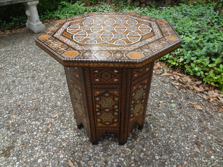 Antique Middle Eastern, Moroccan or Moorish Arabesque style octagonal side table. This beautiful table has a great pattern with alternating intricately inlaid mixed woods and mother-of-pearl in striking geometric pattern. Detailed and edged in camel