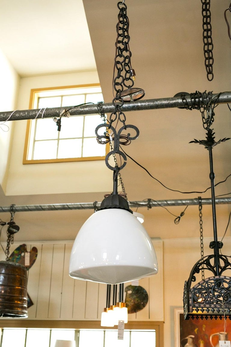 Antique milk glass and forged iron pendant light from France (circa 1930-1950). The pendant is delightful due to the contrast between its simple, Classic shaped glass shade and its detailed forged ironwork. A bit smaller-than-usual, it's the perfect