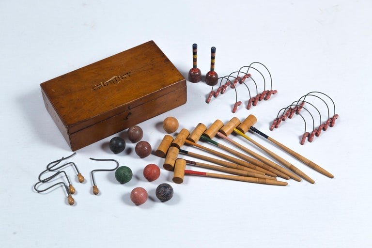 Charming antique mini wood croquet set with hinged wooden box. Eight mallets, eight balls, two stakes, and wickets.