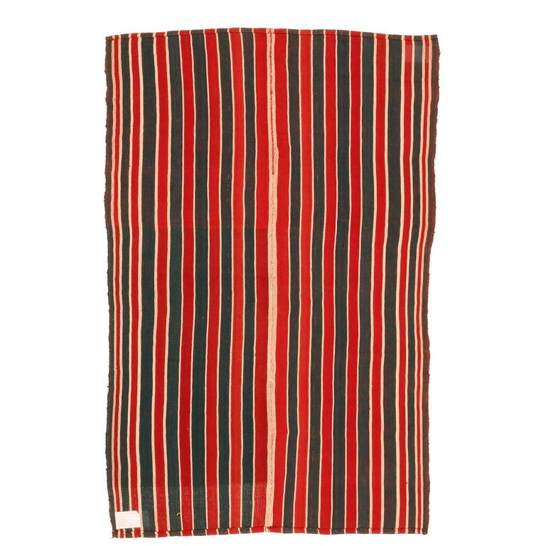 A very graphic tribal Kilim composed of two joined panels each containing a sequence of green and red vertical stripes of various widths, each framed by a narrow ivory stripe. The result is a wool flat-weave with a mirror image pattern having a