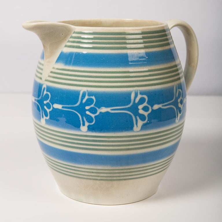 A large antique mochaware pitcher made in England circa 1830 colored with bands of powder blue and olive green slip with an offset decoration of a flower in white slip. In