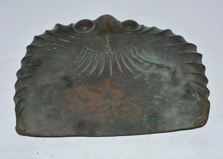 The antique copper dust pan has a molded flared design with two