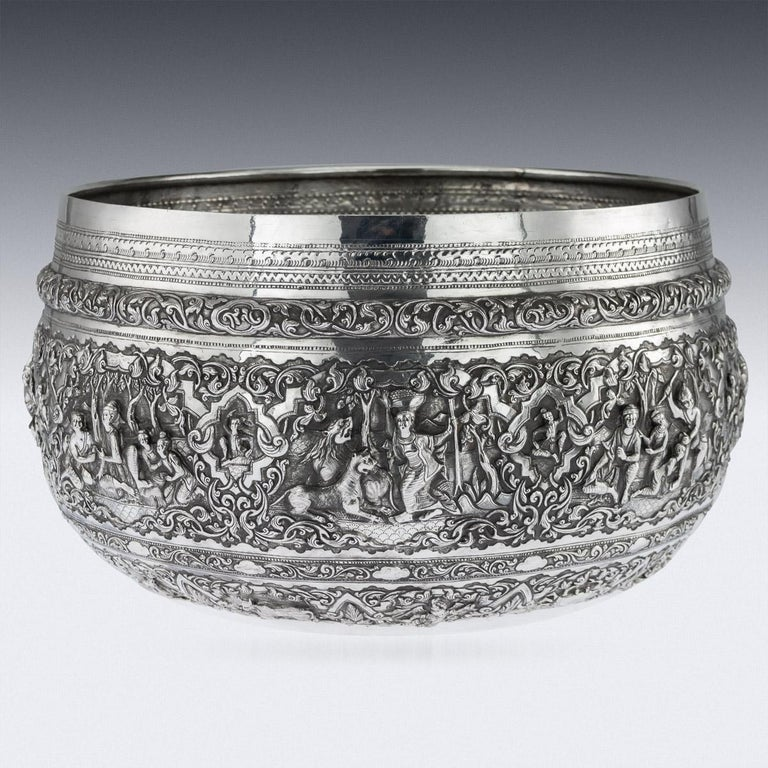 Antique early 20th century monumental Burmese, (Myanmar) solid silver Thabeik bowl, repousse' decorated in high relief with detailed panels depicting different traditional scenes from the Burmese mythology, showing very detailed figures set against